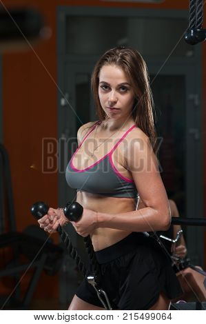 Sexy fitness woman in sportwear and sneakers doing exercises in the gym. Young woman posing with handle of simulator.