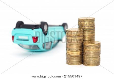 Coins stack with a blue overturned model car and Financial statement. Loan finance concept.
