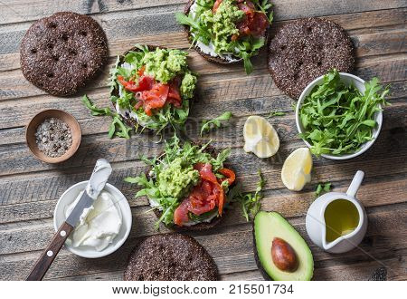 Rye bread sandwich with cream cheese smoked salmon arugula mashed avocado on rustic wooden background top view. Healthy delicious snack breakfast or appetizer