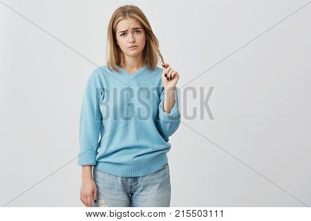 Portrait of upset and dissatisfied young woman with oval face, dark eyes and fair straight hair wearing blue casual sweater, frowning her eyebrows and playing with her hair, being displeased with something.
