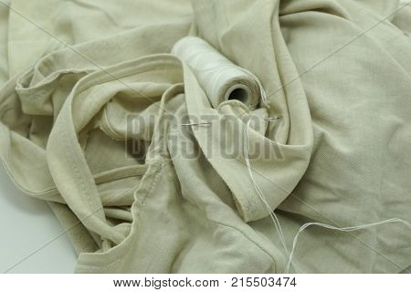Old Tank Top and sewing needle on white background sufficiency economic concept