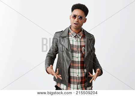 Do you know who I am, man. Portrait of angry black-skinned african guy with curly hair in leather jacket and sunglasses gesticulating with hands, arguing after being offended by man on street.