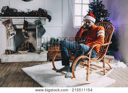 Serious and bored guy is sitting in the rocking chair in the beautiful Christmas decorated room. He is waiting for his friends coming tonight but he doesn't have anuthing to do so he is just sitting and waiting for them.