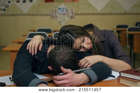 Boring lesson. Lecture. Two bored and lazy students sleep on a school desk table in a classroom.