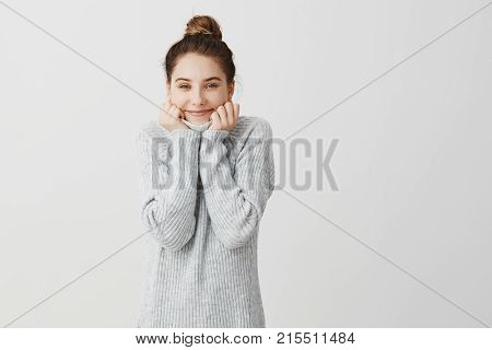 Happy fashionable caucasian girl being satisfied and glad. Female student resting at home after classes wrapping herself up in collar of grey sweater. Happiness and pleasure concept