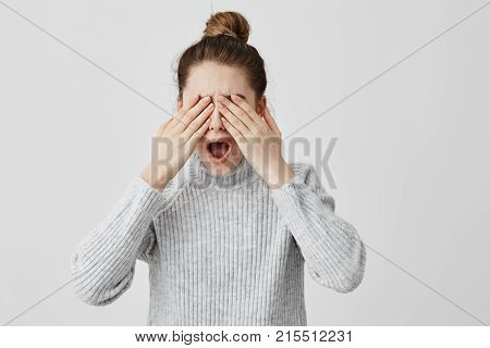Brunette female screaming in fright covering eyes with hands. Young woman feeling fear doesn't want to see what happened. Terror, emotions concept