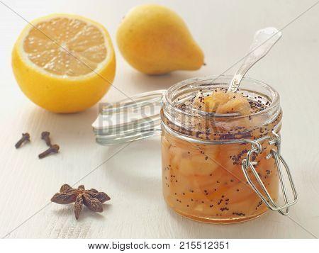 Jar full of pear and poppy seeds jam with fresh lemon. Selective focus on the jar.
