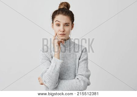 Melancholy girl 20s standing with brooding expression touching her cheek with finger. Frowning female copywriter looking on camera with one eyebrow raised being reflective. Puzzlement