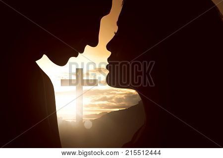 Silhouette Of Young Couple Looking At Each Other With Christian Cross