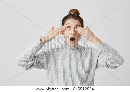 Attractive girl hipster hiding her eyes from sun covering it with hands. Young woman looking up with mouth opened being blinded by sunshine. Body language