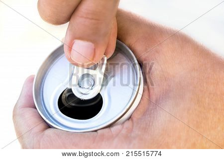 A hand opening a canned beverage with a man hand. Closeup of canned drink pull tab opening.