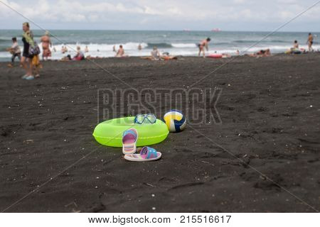Ball colorful sandal and yellow Floating Ring on beach. Blurred photo of people on sand beach. Travel or sea vacations concept. Beach life