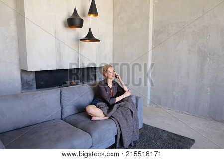 Pretty attractive woman takes phone by hand and spends it on touch screen to answer husband's incoming call, chatting and laughing happily, sitting on gray soft sofa in lotus pose wrapped in plaid in stylish living room with gray walls. European-looking w