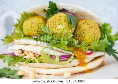 Fresh baked falafel in pita with vegetables sprouts chickpeas and curry sauce. Vegan Healthy Food Concept.
