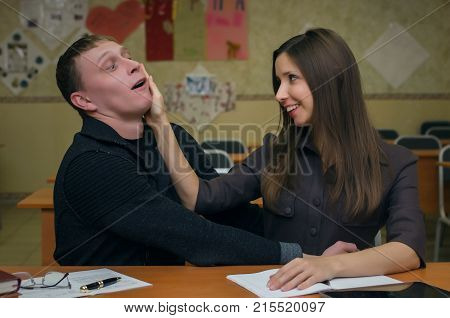 School change. Bad behavior in school concept. Young boy student achieves the attention of his classmate girl. Declaration of love in school.