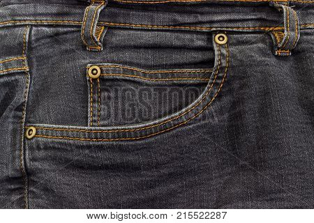 Fragment of the top of the used black jeans with waistband belt loop reinforcing by copper rivets pocket and little pocket