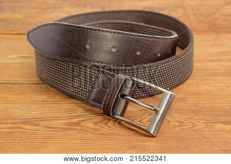 Casual brown elastic stretch belt for men with leather ends and classical buckle at shallow depth of field on an old wooden surface