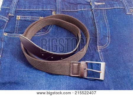 Casual brown elastic stretch belt for men with leather ends and classical buckle lies on a blue jeans