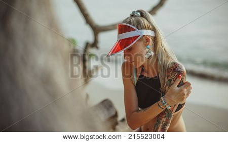 Portrait of a beautiful girl in a red visor closeup. Wearing Large turquoise earrings. Holiday in Thailand On the background of evening beach.