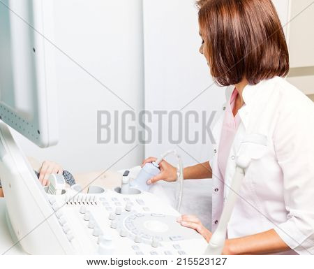 Close-up shot of sonographer scanning young pregnant woman's belly with ultrasonic transducer doing obstetric ultrasonography poster