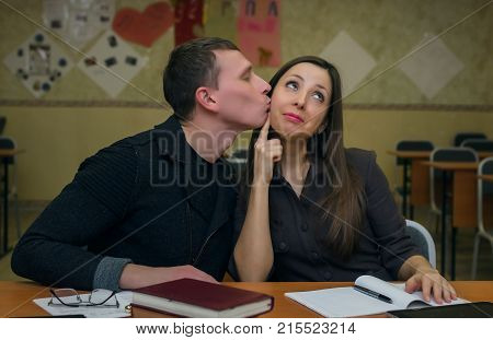 Young man student confesses love to his girlfriend classmate and kisses her. School love concept.