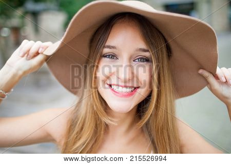 Positive attractive girl with pretty smile looking at camera and adjusting brown sunhat outdoors. Portrait of happy stylish young woman enjoying life. Walk concept
