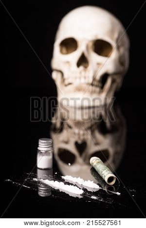 cocaine or other illegal drugs that are sniffed by means of a tube and Skull isolated on black glossy background