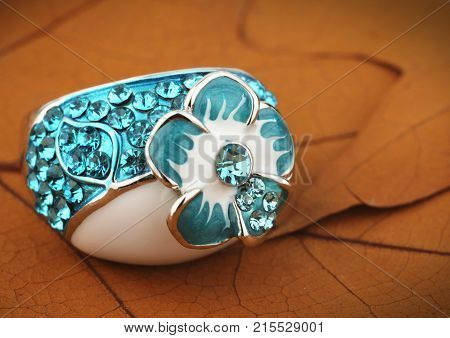 Jewelery ring with gemstone on yellow leaves