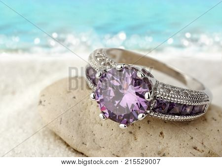 Jewelery ring with violet gemstone on sand beach