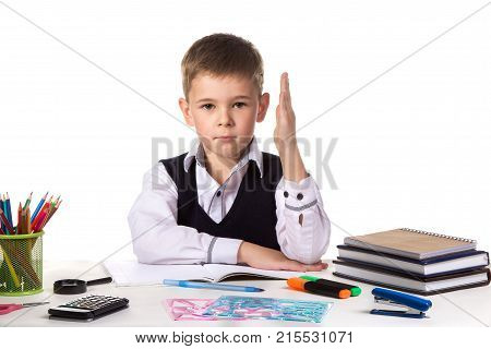 Humble excellent pupil with hand up sitting at the table on the white background.