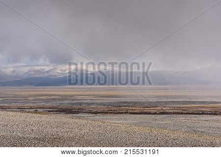 A picturesque view of a heavy snowfall over the mountains a steppe and a village in the distance on the background of a sky with storm clouds