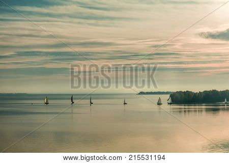 Sunrise over the river with yachts on a calm water surface in the summer time