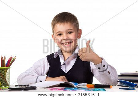 Cheerful satisfied pupil sitting at the desk with thumb up surrounded with stationery.