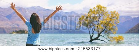 Happy wellness freedom woman in New Zealand winning with arms up in success at Wanaka Lone Tree, popular travel destination. Happiness in life concept. Panoramic banner of joyful girl.