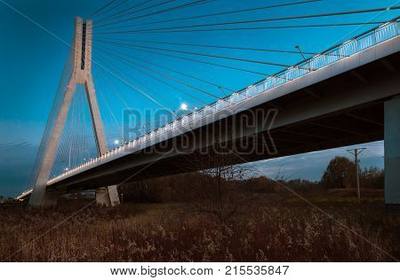 Cable-stayed bridge close-up in the evening against a background of blue sky and clouds