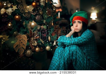 Bored Girl Waiting for Santa Claus Next To Her Christmas Tree