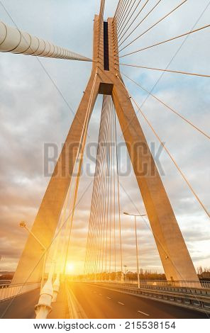 Highway going through a cable-stayed bridge with big steel cables, close-up in the evening during a sunset against a background of sky, clouds and sun rays