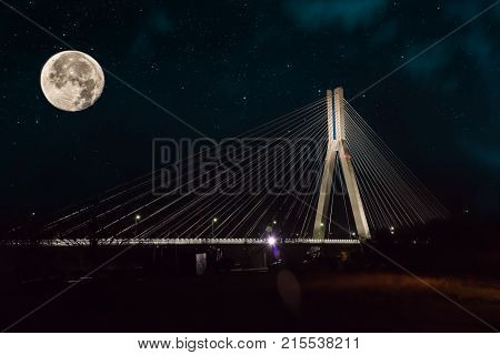Cable-stayed bridge close-up at night against the background of the starry sky, moon and clouds