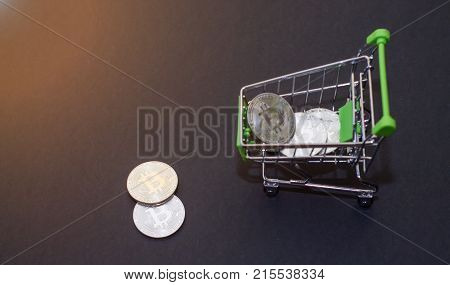 Shop trolley for purchases with bitcoins. Crypto currency bitcoin on a black background. Empty space for text.