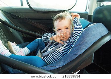 Baby Smile In A Safety Car Seat. Security. One Year Old Child Girl In Blue Wear Sit On Auto Cradle.