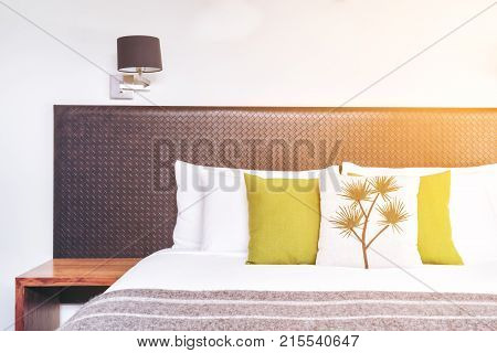 Bed headboard design in bedroom interior with pillows and blanket on the bed. Close up view of Australian-style bedroom with cozy interior design for hotel home and resort accommodation business.