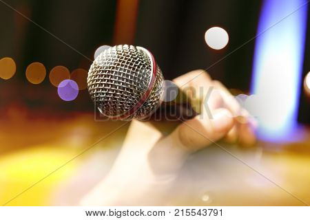 Live music background. Karaoke and microphone concept. Stage lights and singer.