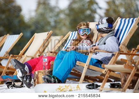 Male and female child enjoys in sun lounger on ski terrain