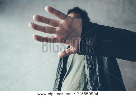 Celebrity male hiding face with hands from paparazzi photographers no photos gesture