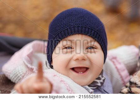 closeup portrait of smiling little girl with only two teeth in the autumn park. Baby girl laughing. Happy childhood, one year old child, autumn season, outdoors concept