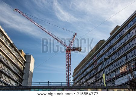 Inner city construction industry. Massive red crane between office buildings. Commercial infrastructure.