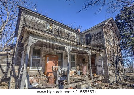 abandoned two-story wood house with objects on front porch; rural Kansas