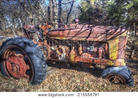 abandoned red tractor in leaves, rural Kansas