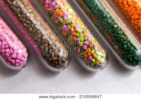 Plastic Pellets .polymeric Dye In Test Tubes On Gray Background.