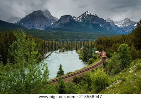 Train passing through the Morant's Curve in bow valley with Rocky Mountains in the background, Banff National Park, Alberta Canada.